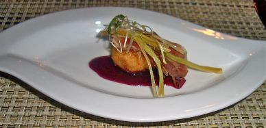 Risotto ball on beetroot coulis topped with crispy parma ham