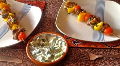 The grilled skewers basted with leftover marinade and served with the raita